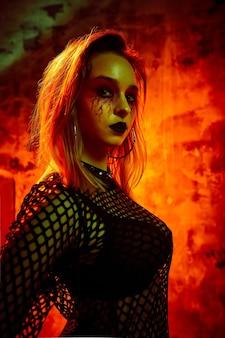Modèle féminin en tenue d'halloween posant avec sur fond rouge. une fille magnifique en vêtements célèbre le jour des morts. concept d'halloween, costume de sorcière, couleurs vives, steam punk.