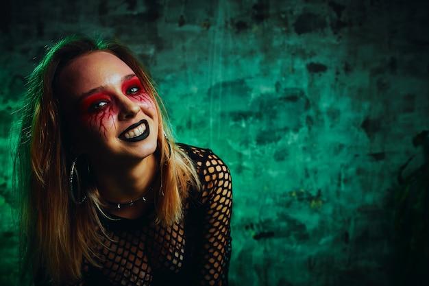 Modèle féminin en tenue d'halloween posant avec sur fond rouge. superbe fille en vêtements célèbre le jour des morts. concept d'halloween, costume de sorcière, couleurs vives, steam punk.
