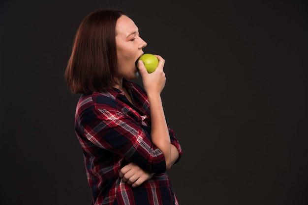Modèle féminin en tenues de collection automne hiver tenant une pomme verte et en prenant une bouchée.