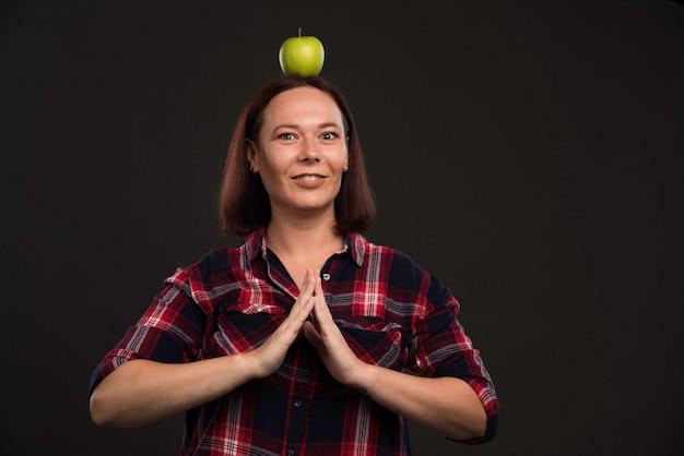 Modèle féminin en tenues de collection automne hiver tenant une pomme verte sur la tête et priant.