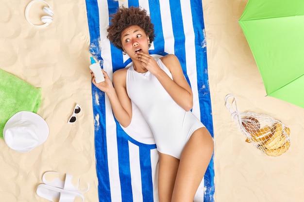 Le modèle féminin tient une crème solaire a la peau brûlée après un long bain de soleil porte des poses de bikini blanc sur du sable blanc entouré d'accessoires de plage. coup de soleil