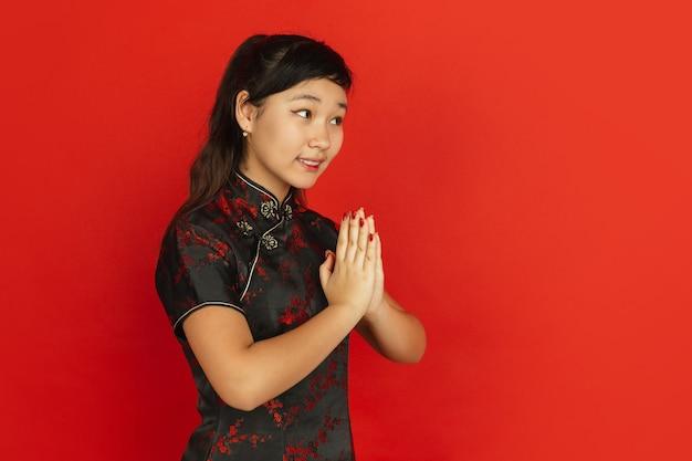Modèle féminin en vêtements traditionnels faisant des gestes, merci à côté