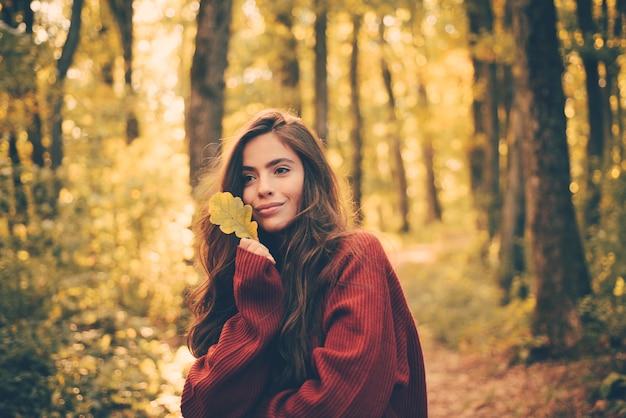 Modèle de femme automne romantique. portrait de la belle femme caucasienne marchant à l'extérieur. femme d'automne s'amusant dans le parc et souriant