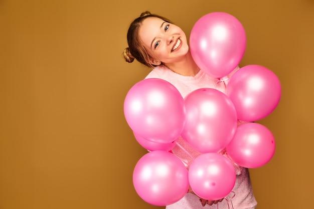 Modèle femme avec des ballons à air rose sur mur d'or