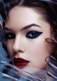 Modèle femme beauté avec maquillage et cheveux bouclés à travers un miroir créatif dans des tons froids sur fond gris