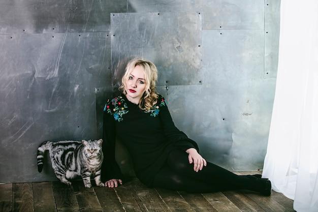 Modèle femme belle et à la mode avec un chat sur un fond de mur métallique dans le studio
