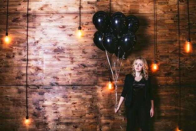 Modèle femme belle et à la mode sur le fond d'un mur en bois avec ballon d'éclairage horizontal