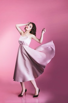 Modèle femme belle et à la mode en robe rose sur fond rose