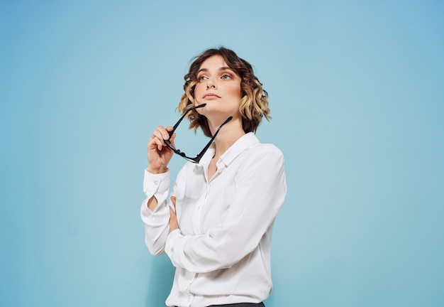 Modèle femme en chemise blanche sur fond bleu tient des lunettes à la main