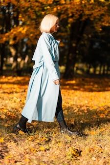 Modèle de femme élégante en manteau bleu à la mode avec des bottes se promène dans le parc avec un feuillage d'automne jaune par une journée ensoleillée d'automne