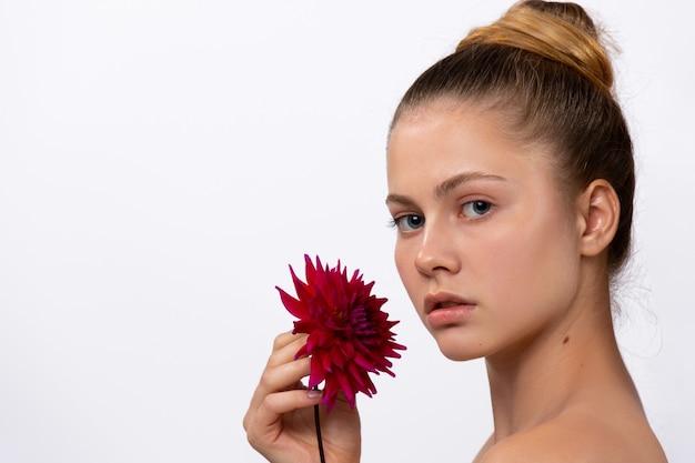Modèle de femme mignonne avec une fleur de couleur bordeaux dans sa main posant sur un espace latéral de mur blanc
