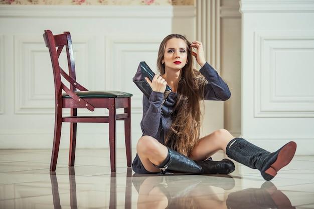 Modèle femme en robe avec des bottes à la mode et des lèvres rouge vif en intérieur vintage