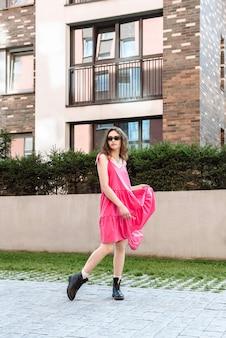 Modèle femme en robe rose posant à l'extérieur de la ville