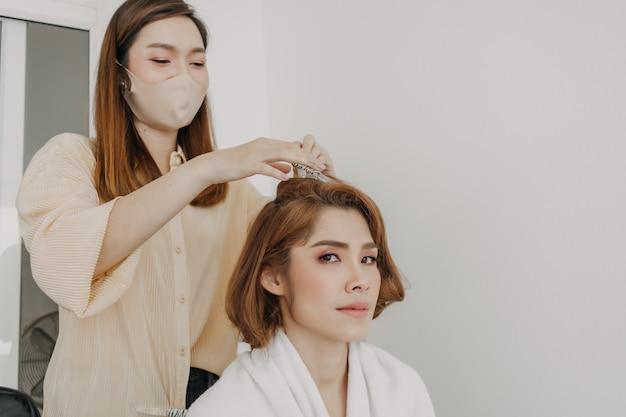 Le modèle de femme s'habille des cheveux par le coiffeur dans la salle de studio
