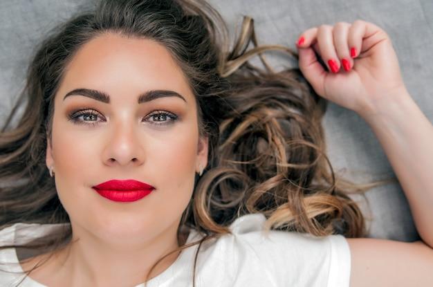 Modèle de femme sensuelle avec des cheveux bruns volants balayés par le vent sur fond gris clair. coiffure brillante et longue santé. beauté et soins capillaires. maquillage naturel de la mode