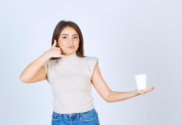 Un modèle de femme souriante montrant un gobelet en plastique et faisant le geste de parler au téléphone.