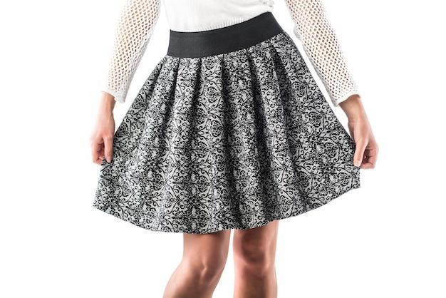 Modèle femme tient dans ses mains sa belle jupe à carreaux posant en studio sur blanc