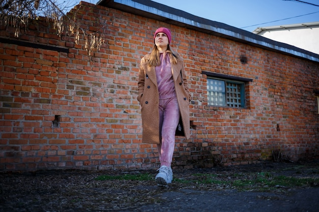 Modèle de fille élégante dans un manteau marron, un costume rose et des bottes grises sur les ruines de la ville. les tendances de la mode moderne. image à la mode