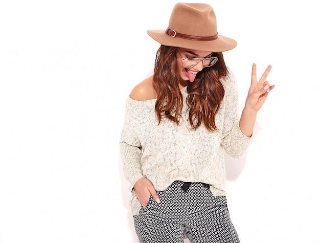 Modèle fille élégante dans des vêtements d'été décontractés en chapeau brun avec du maquillage naturel dans des verres isolés., montrant sa langue et signe de paix