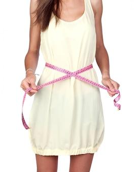 Modèle fille avec un ruban à mesurer isolé sur fond blanc