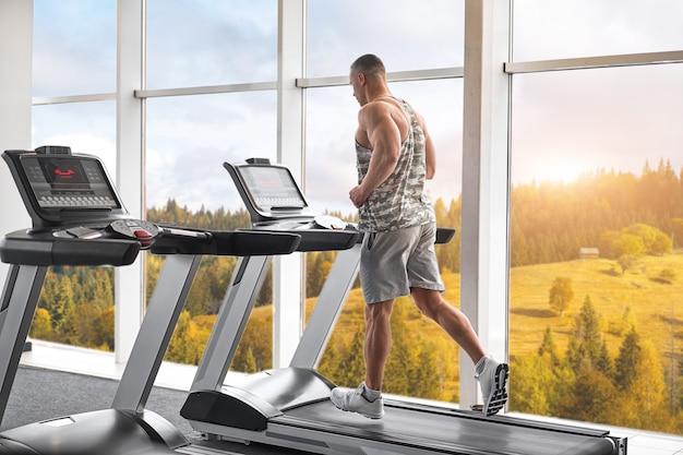 Modèle de fitness bodybuilder athlétique musclé exécutant une salle de sport sur tapis roulant près d'une grande fenêtre