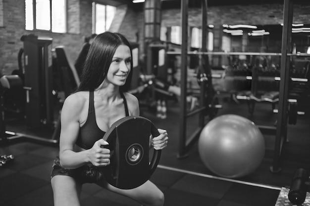 Modèle de fitness sexy faisant des exercices de squat avec haltères dans les mains de la salle de gym. concept de formation fonctionnelle