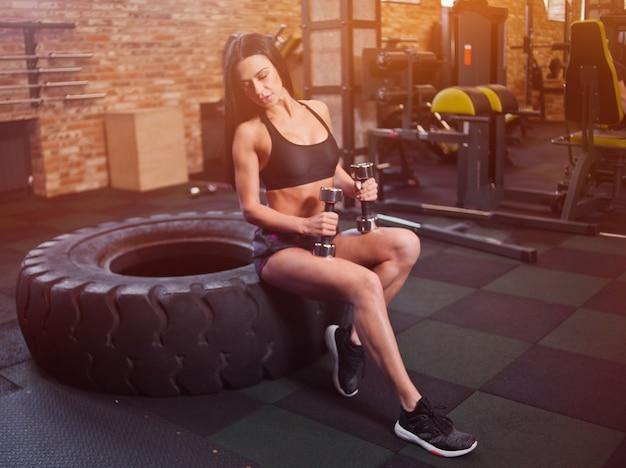 Modèle de fitness sexy tenant des haltères dans les mains et assis sur une grande roue dans la salle de gym. concept de formation fonctionnelle