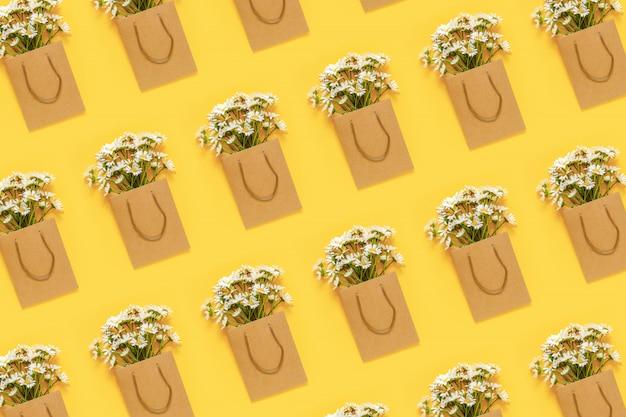 Modèle avec des fleurs de camomille des champs en emballage artisanal sur fond jaune.