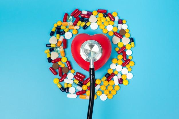 Un modèle en forme de coeur d'un stéthoscope et un grand nombre de médicaments qui l'entourent