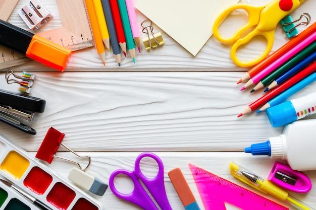 Modèle de fournitures scolaires sur un fond en bois blanc