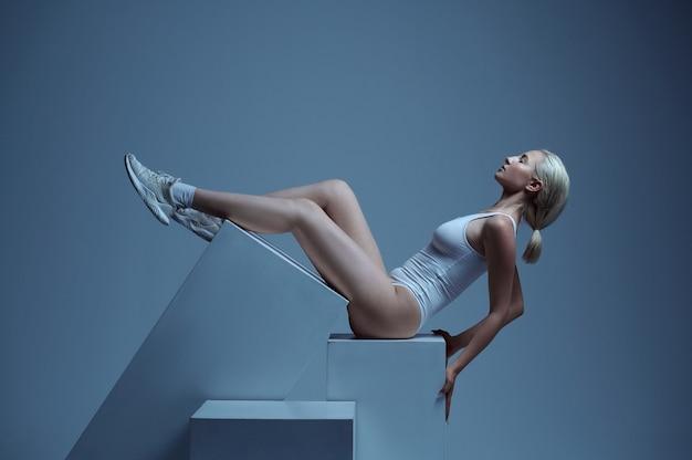 Modèle futuriste sexy allongé sur des cubes, futurisme
