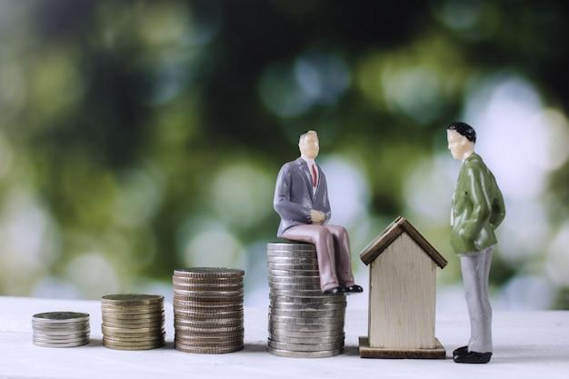 Modèle de gens d'affaires avec des pièces d'argent et de la maison