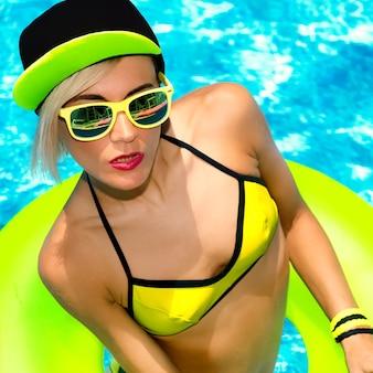 Modèle glamour dans un style de fête d'été chaud à la piscine