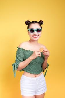 Modèle glamour élégant belle jeune femme avec des lèvres rouges tenant un cookie sur fond jaune.