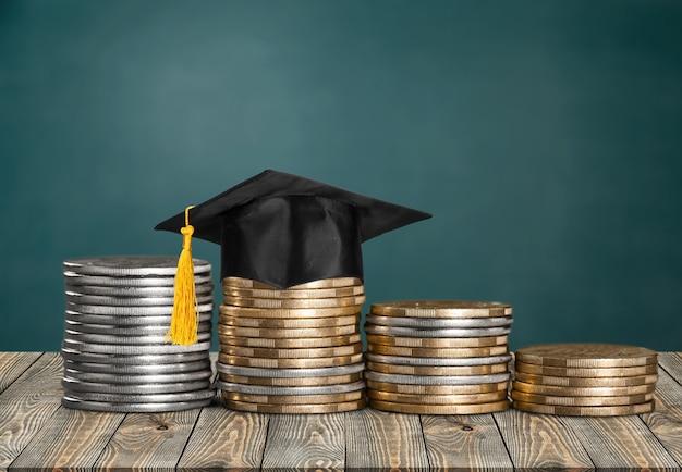 Modèle de graduation de chapeau sur les pièces d'argent économisant pour l'éducation et les bourses d'investissement de concept