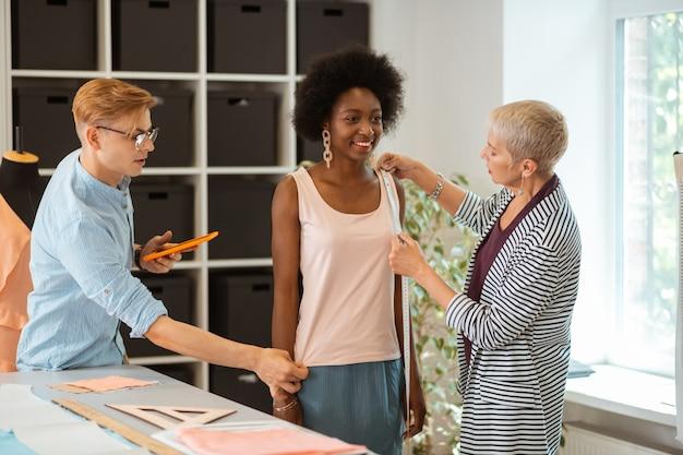 Modèle heureux debout en compagnie de deux créateurs de mode prenant ses mesures