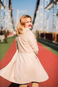 Le modèle heureux porte un manteau beige et une écharpe blanche