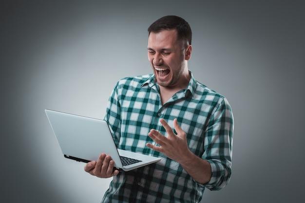 Modèle d'homme d'affaires attrayant en chemise verte isolé sur gris travaillant avec un ordinateur portable, montrant quelque chose de la main gauche.