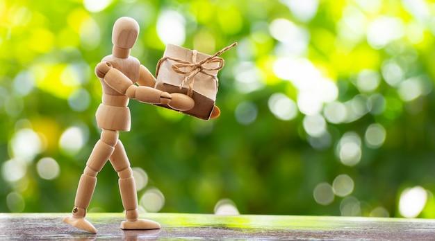 Un modèle homme en bois tenant un coffret cadeau