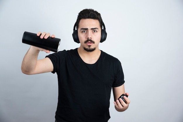 Modèle homme brune dans les écouteurs tenant une tasse vide.