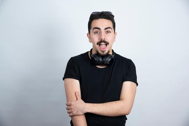 Modèle homme brune debout dans les écouteurs contre le mur blanc.