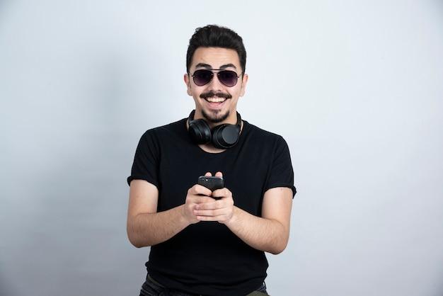 Modèle homme brune debout dans les écouteurs et tenant le téléphone mobile.