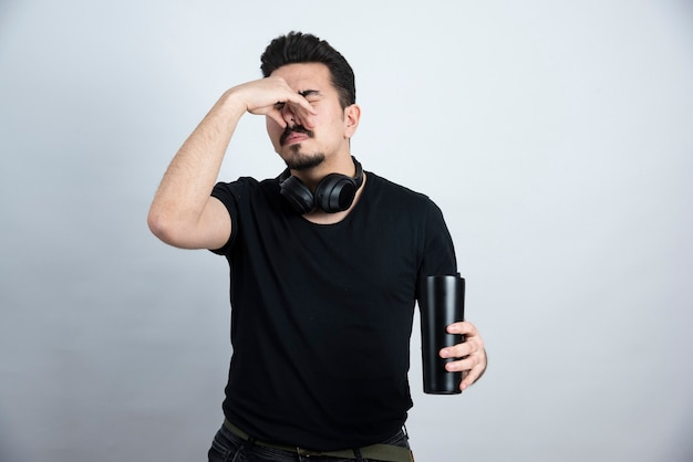 Modèle homme brune tenant une tasse et fermant le nez avec dégoût.