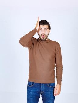 Un modèle d'homme choqué debout et tenant sa tête sur un mur blanc. photo de haute qualité