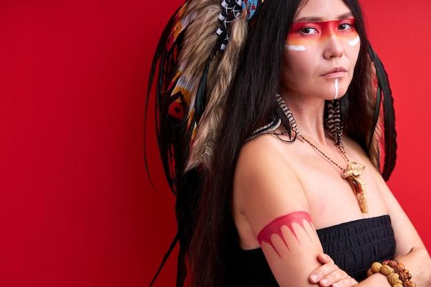 Modèle indien fantastique stand avec les bras croisés isolé sur mur rouge, jeune femme en haut avec des peintures sur le visage, portant des plumes sur la tête