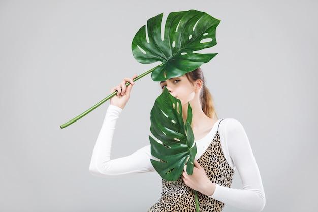 Modèle de jeune belle fille avec portrait de feuilles tropicales sur fond blanc en studio