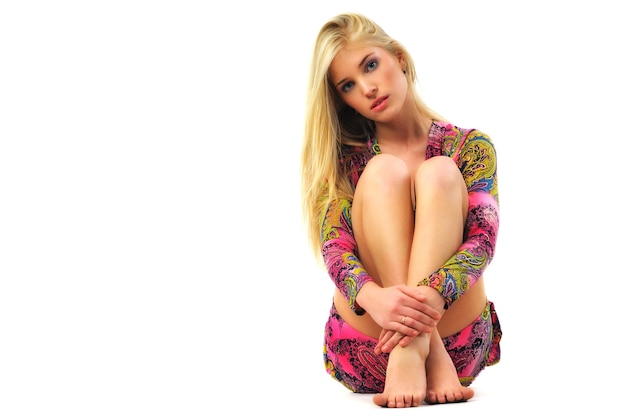 Modèle de jeune femme belle blonde en robe rose avec motif oriental assis sur le sol et embrassant les jambes
