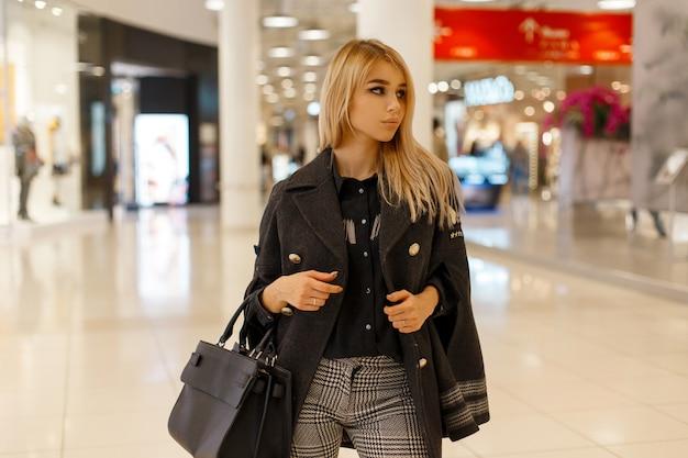 Modèle de jeune femme blonde moderne dans un manteau à la mode chic