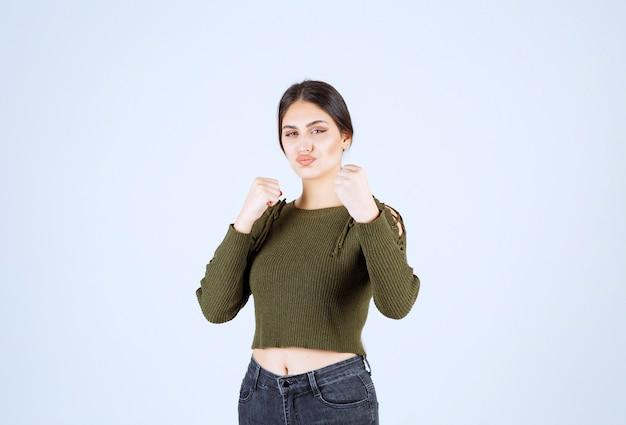 Un modèle de jeune femme charmante en vert montrant comment frapper