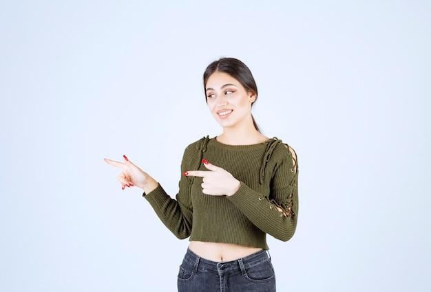 Un modèle de jeune femme charmante en vert pointant à ses côtés